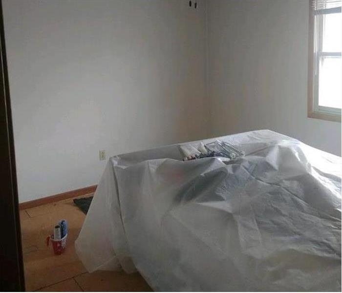 A bed properly wrapped and a fresh painted white room