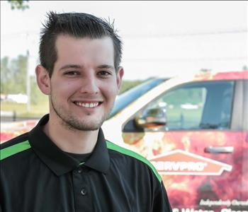 Male employee Dan Burke in front of a SERVPRO truck in the background
