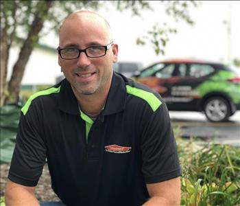 Male employee John Alessio in front of SERVPRO car