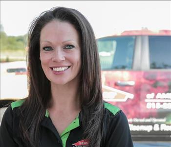 Female employee Lori Newhouse in front of SERVPRO truck in background