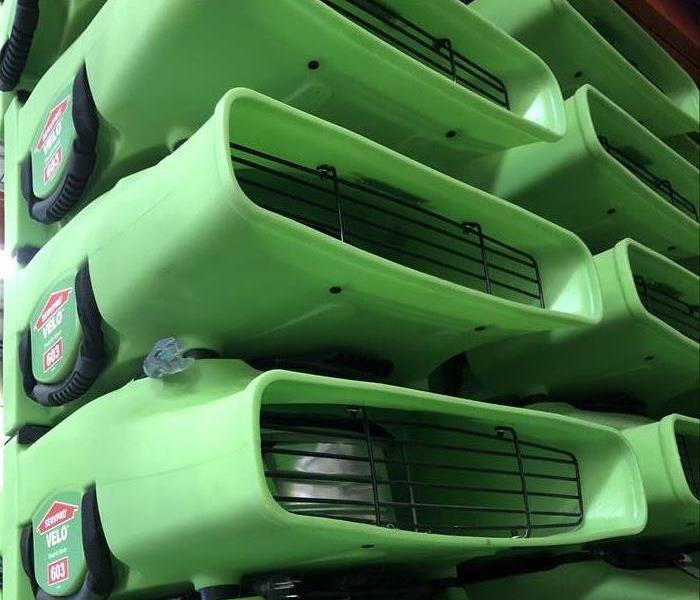 stack of green SERVPRO air movers for drying