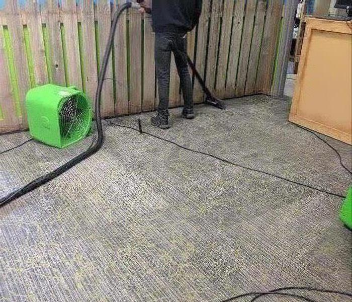 air mover drying carpet in area business after a storm
