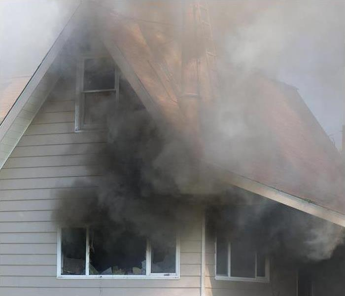 Smoke billowing from windows of a house