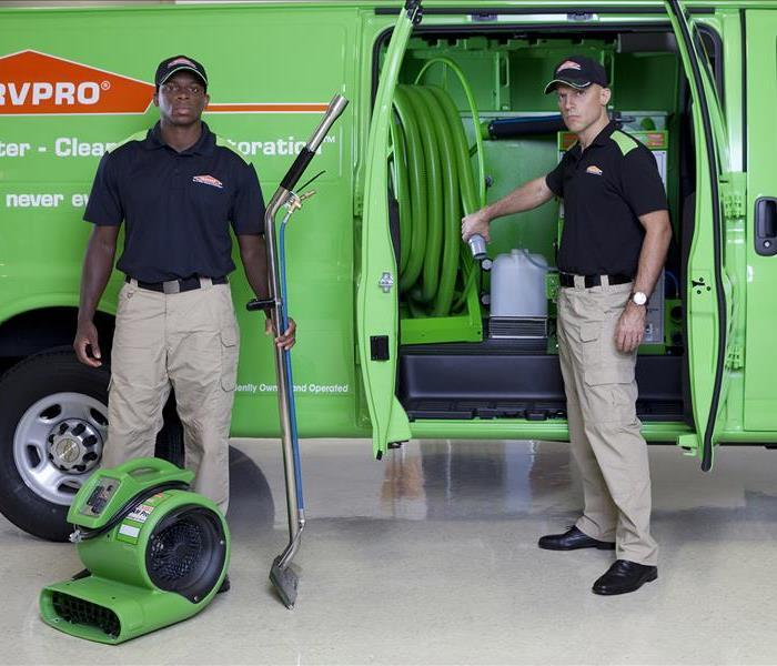 Two SERVPRO team members standing in front of a SERVPRO van
